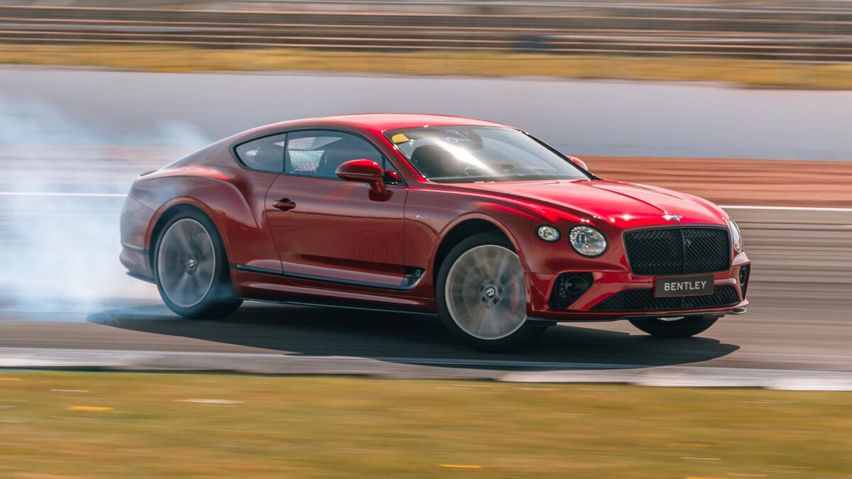 The Bentley Continental GT Speed skids across the tracks, smoke coming out of its rear wheels