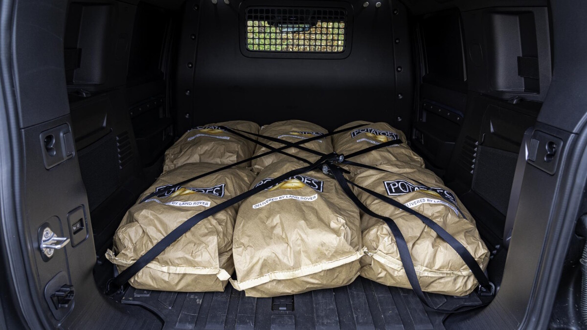 The Land Rover Defender Hard Top cargo bed filled with sacks of produce