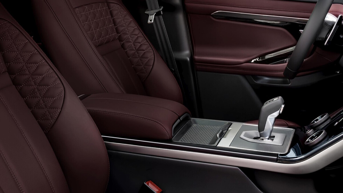 The interior of the Range Rover Evoque featuring the driver's seat, gear stick, and steering wheel.