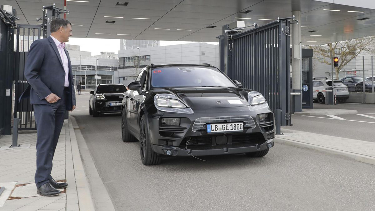 The Porsche Macan EV on the road with a man standing by the roadside
