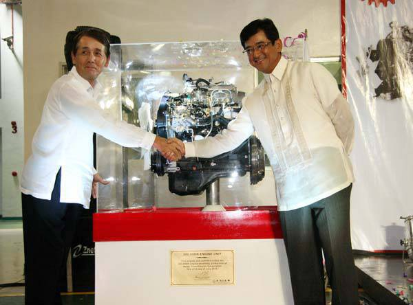 TopGear.com.ph Philippine Car News - Mitsubishi Motors Philippines president and chief executive Masahiko Ueki and Asian Transmission president and chief executive Kenji Ichimiya pose behind the 300,000th engine unit during the milestones celebration at Asian Transmission's plant in Calamba, Laguna.