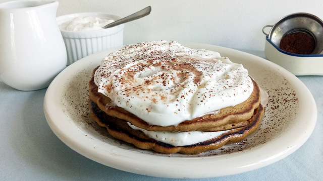Coffee pancake recipe becomes dessert with a cream cheese whipped cream, a dusting of cocoa powder, and a drizzle of rum-infused syrup.