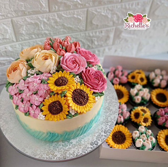 This cake is topped with edible sunflowers, hydrangeas, apple blossoms, and other flowers you might find in a bouquet.